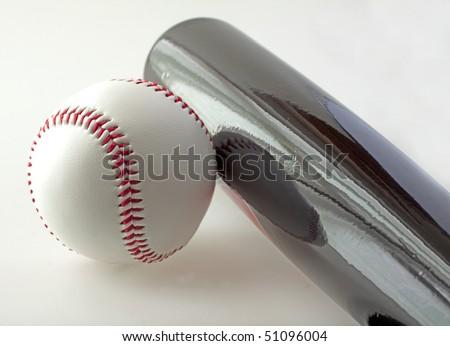 A baseball near a bat on a gray background - stock photo