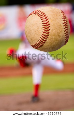A baseball player pitching (focus on the ball) - stock photo