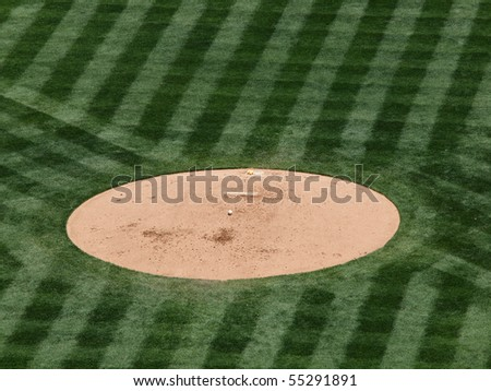 a baseball rest on a mound in the middle of the game.  With pattern lines cut into the grass around the pitching mound. - stock photo