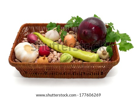 A basket full of beans, onion, garlic with green peppers, radishes, cabbage and parsley isolated on white background - stock photo