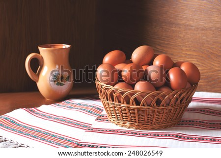 A basket full of fresh hen eggs from a private farm. Eggs on wooden background and white towel. Food photography - stock photo