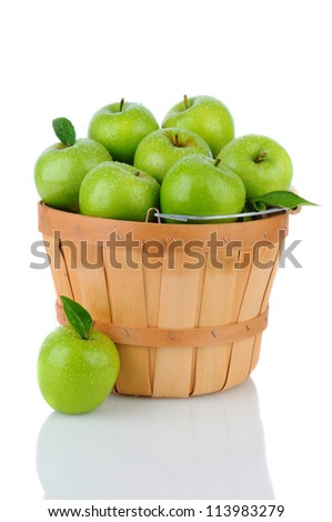 A basket full of fresh picked Granny Smith. Vertical format over a white background with reflection. - stock photo