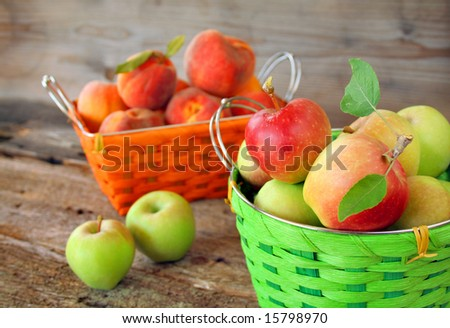 A basket of apples and a basket of peaches with a rustic surrounding.  Focus is on the basket of apples.