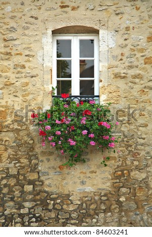 A basket of bright pink and red flowers hangs on the window of a home in an ancient building in France, surrounded by beautiful patterns in the stone wall. - stock photo