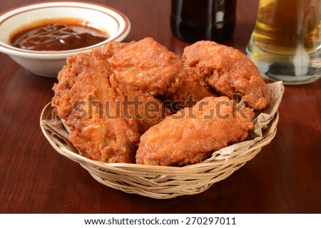 A basket of chicken wings with barbecue sauce and beer - stock photo