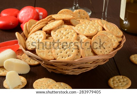 A basket of crackers with cheese and wine - stock photo