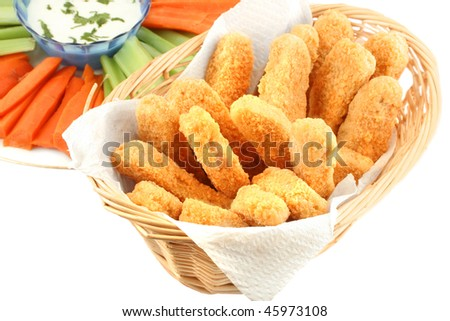 A basket of crispy chicken fingers with platter of vegetables and ranch dip on a white background - stock photo