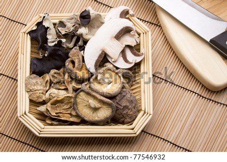 A basket of fresh and dried woodear, portobello, crimini and shitake mushrooms. - stock photo