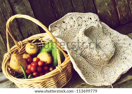 A basket of fresh picked organic vegetables and a straw hat on a grunge wood background. - stock photo