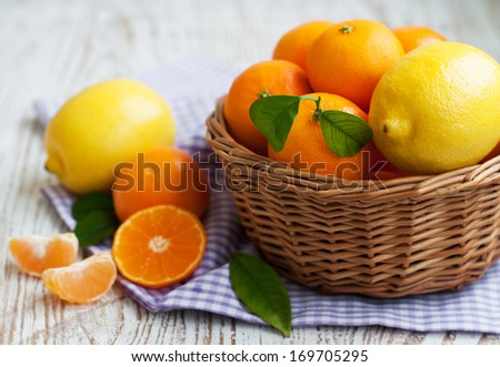 A basket of fresh tangerines and lemons on a wooden background