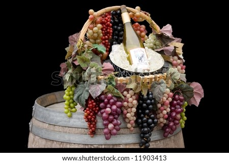A basket of grapes with a bucket of ice and a bottle of wine sitting on top of a barrel. - stock photo
