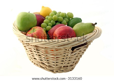 A basket of mixed green fruits, apple, lime, and grapes…