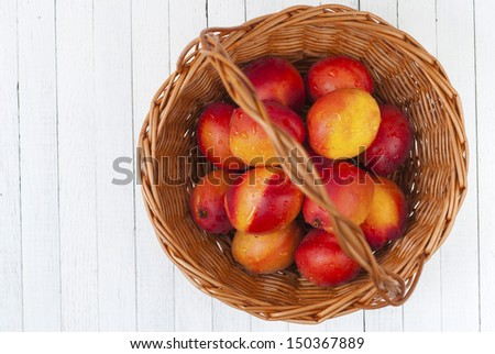 a basket of nectarines on white wooden table - stock photo