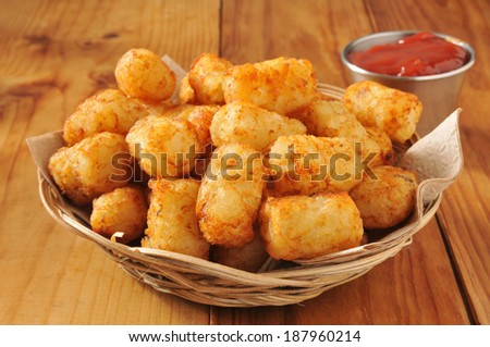 A basket of tater tots on a rustic wooden counter