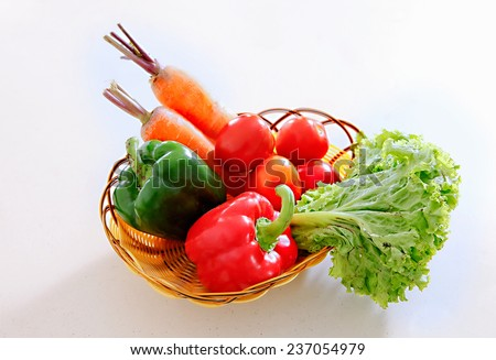A basket of vegetables, carrot, tomatoes, salad and capsicum  - stock photo