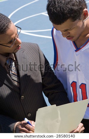 A basketball coach in a business suit sharing a play with a player on the team.   He could be also be recruiter trying to get him to sign a contract. - stock photo