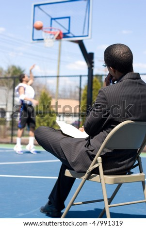 A basketball coach or scout recruiter observes an athlete while he warms up.