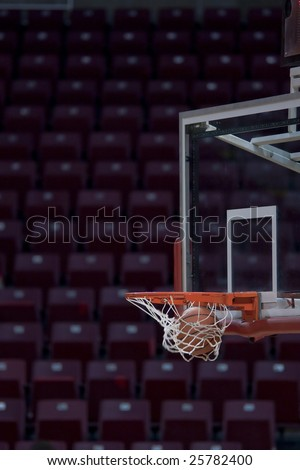 a basketball going through the hoop into the net - stock photo