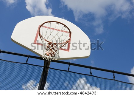 A basketball hoop in a children's playground stands against a partly cloudy blue sky.