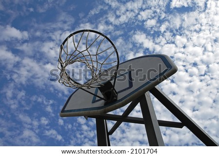 A basketball hoop is set against a beautiful blue cloudy sky.