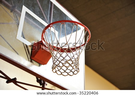 A basketball hoop with a glass backboard in an empty gym - stock photo
