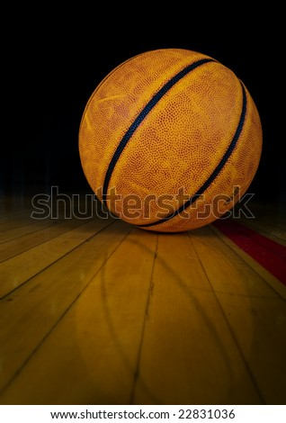 A basketball on a dark gym floor with reflection