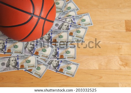 A basketball on a pile of one hundred dollar bills viewed from above - stock photo