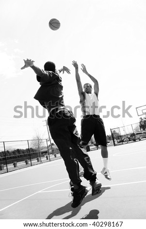 A basketball player shooting the ball at the basket while being guarded by his opponent. - stock photo
