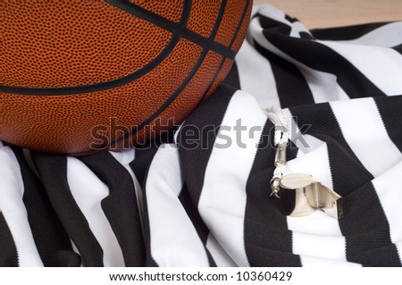 A basketball referees items including a ball, a striped jersey and a whistle - stock photo