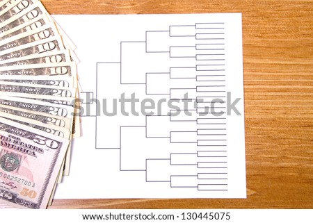 A basketball tournament bracket and fanned money. - stock photo
