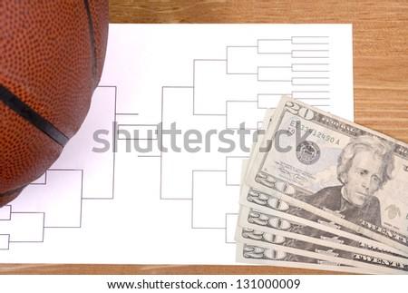 A basketball, tournament bracket and twenty dollar bills - stock photo