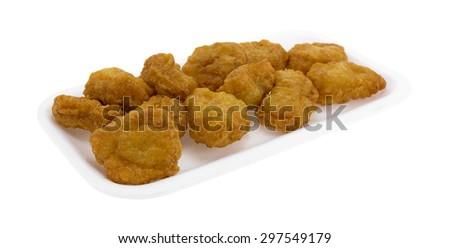 A batch of crispy chicken nuggets in original tray. - stock photo