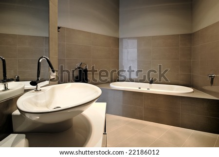 A bathroom with wash basin in the foreground and bath in the background. - stock photo