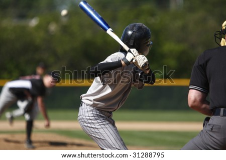 A batter about to hit a pitch during a baseball game.