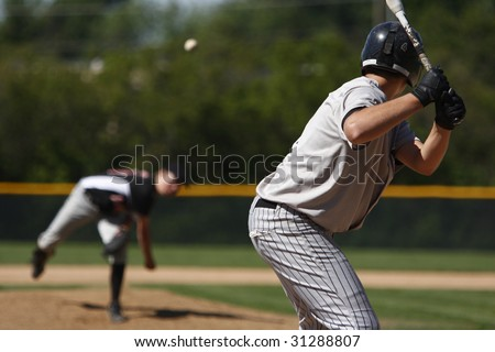 A batter about to hit a pitch during a baseball game. - stock photo