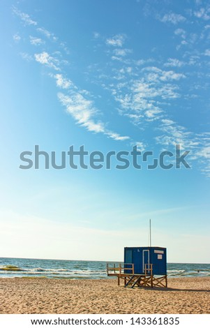 A baywatch tower by the sea with bright blue sky - stock photo