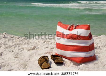 A beach bag and sandals on the sand near the ocean - stock photo