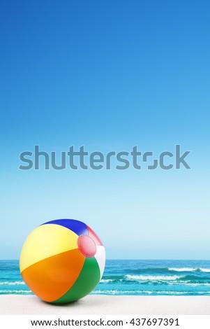 A beach ball on a beautiful white sand beach in summer. - stock photo