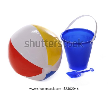 A beach ball with a blue sand pail and shovel.  Isolated on white. - stock photo