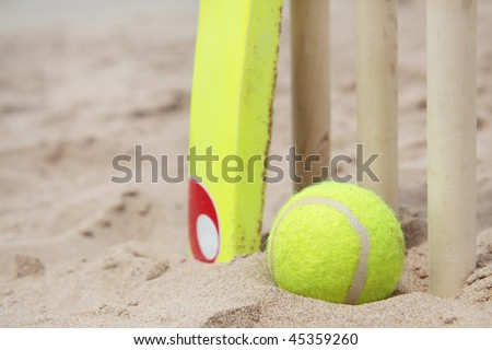 A beach cricket set with tennis ball on the sand. - stock photo