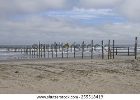 A beach made off limits to vehicles by a gated fence running across the beach and into the ocean in the Outer Banks of North Carolina - stock photo