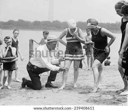 A beach official checks the amount of thigh exposed by a young ladies bathing suit in 1922. The hemlines on all women's clothing reached new heights in the 1920's.