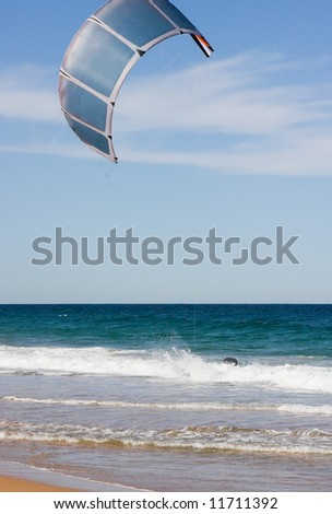 A beach scene with a surf kite in the air
