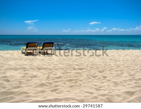A beach scene with blue heaven, clouds and turquoise water - stock photo
