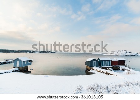 A beach south of Gothenburg, Sweden (Scandinavia) is covered in snow after heavy snowfall in December. You see little houses that are used in the summer to change clothes.   - stock photo