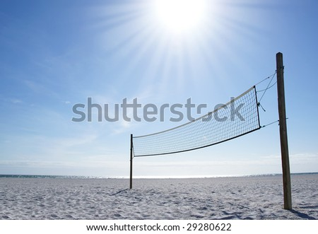 A beach volleyball net on a sunny day, on an empty beach - stock photo
