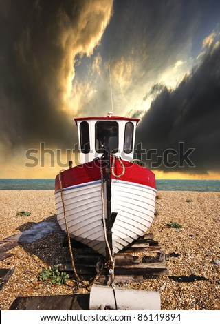a beached fishing boat waiting for the tide on a shingle beach with the sea and a dramatic sky in the background - stock photo
