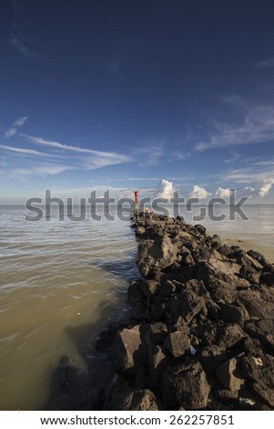 A Beacon at the Tip of the Curvy Rocky Path - stock photo