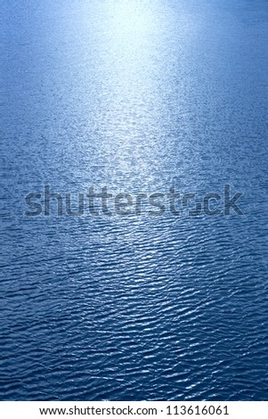 A beam of sunlight reflecting over rippled blue water - stock photo