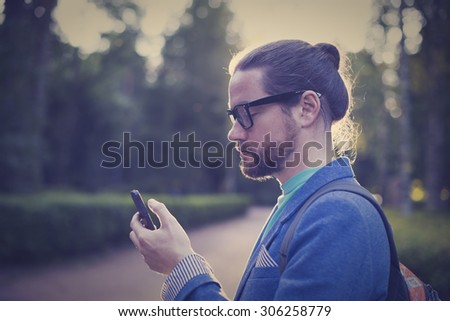 A bearded man in a jacket and glasses clicks on the phone or reading a text - stock photo